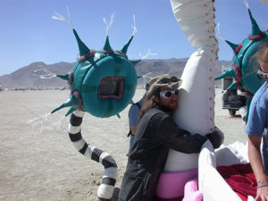 Burning Man Participant hugging fang of the Mouth bed